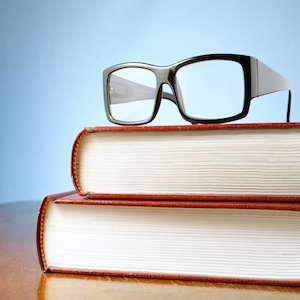 book and black-rimmed glasses on a table